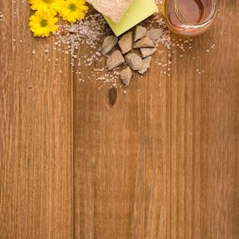 Una vista aérea de flores amarillas; sal; piedras; esponja; lufa y botella de miel sobre fondo con textura de madera