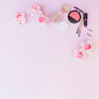 Una vista aérea de flores falsas con productos cosméticos sobre fondo rosa