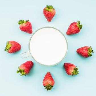 Vista aérea de fresas y leche sobre fondo azul