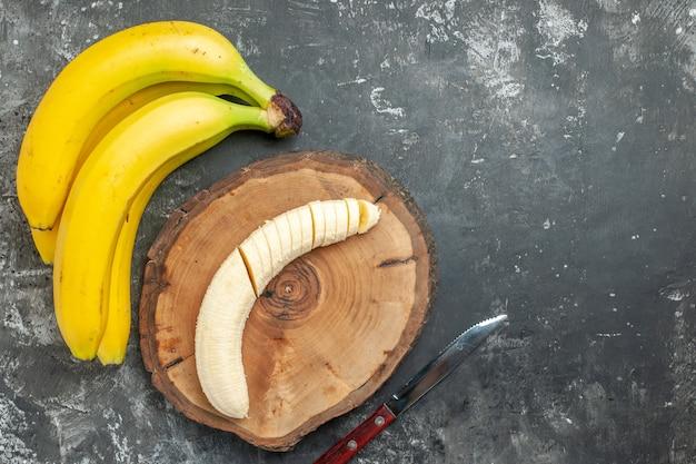 Vista aérea fuente de nutrición paquete de plátanos frescos y picados en un cuchillo de tabla de cortar de madera sobre fondo gris
