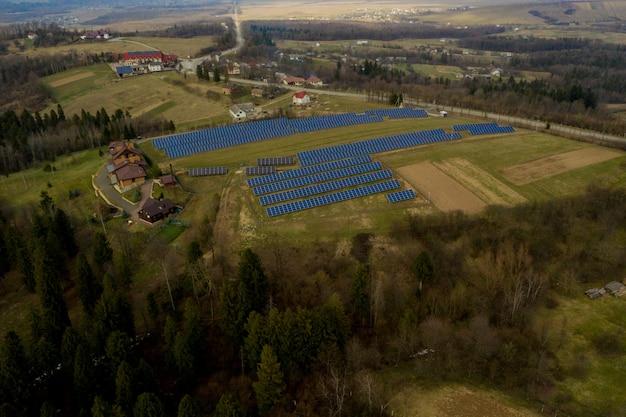 Vista aérea del gran campo del sistema de paneles fotovoltaicos solares que produce energía limpia renovable en el fondo de hierba verde.