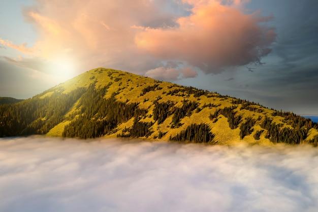 Vista aérea de una gran montaña sobre densas nubes blancas al amanecer brillante.