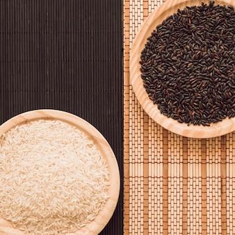 Vista aérea de granos de arroz marrón y blanco en mantel individual