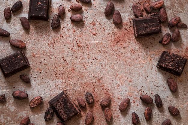Vista aérea de granos de cacao dispersos y trozos de barra de chocolate