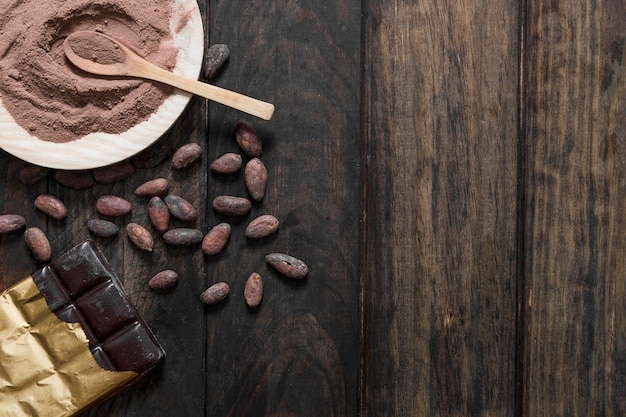 Vista aérea de granos de cacao tostados y polvo con barra de chocolate en la mesa de madera