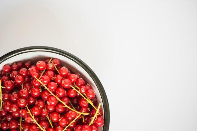Una vista aérea de grosellas rojas frescas en el tazón sobre fondo blanco
