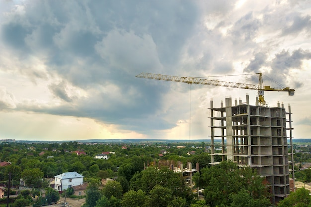 Vista aérea de la grúa de elevación de la torre y el marco de hormigón del edificio residencial de apartamentos altos en construcción en una ciudad. desarrollo urbano y concepto de crecimiento inmobiliario.