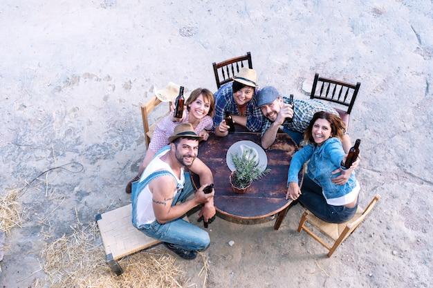 Vista aérea de un grupo de amigos sentados alrededor de una mesa con cervezas