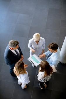 Vista aérea de un grupo de gente de negocios trabajando juntos y preparando un nuevo proyecto en una reunión en la oficina