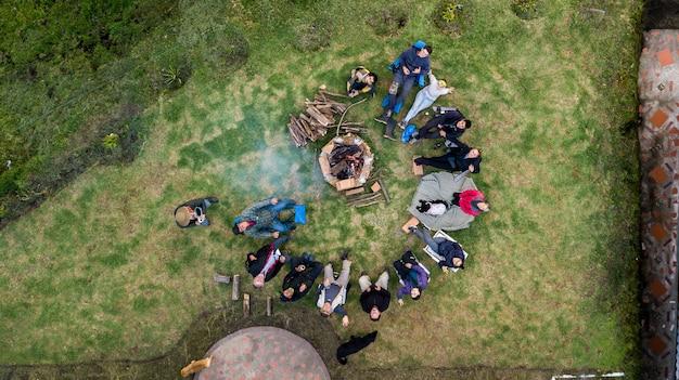 Vista aérea de un grupo de personas que rodean la fogata en el camping.
