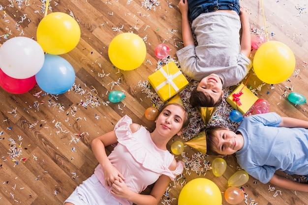 Vista aérea de hermanos felices tumbados con globos; caja de regalo y confeti en piso.