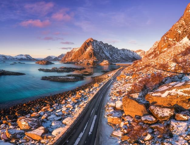 Vista aérea de la hermosa carretera de montaña cerca del mar, montañas, cielo púrpura al atardecer