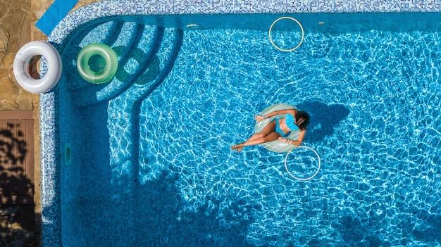 Vista aérea de la hermosa niña en la piscina desde arriba, nadar en anillo inflable donut y se divierte en el agua en vacaciones familiares en el complejo vacacional tropical