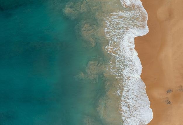 Vista aérea de las hermosas olas del océano que se encuentran con las arenas en la playa