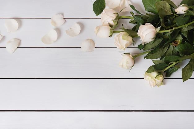Una vista aérea de hermosas rosas blancas frescas en mesa de madera