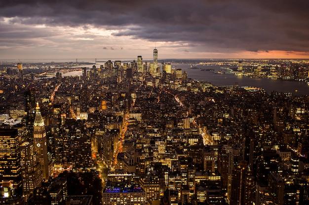 Vista aérea de un hermoso paisaje urbano con edificios iluminados y un mar bajo las nubes de tormenta
