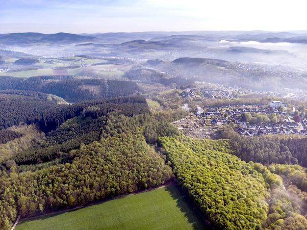 Vista aérea de hermosos campos verdes y casas del campo en un día soleado