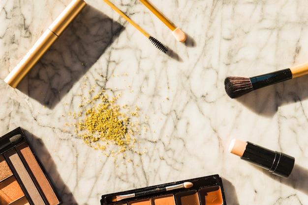 Vista aérea de herramientas de maquillaje profesional y polvos para el rostro sobre un fondo de mármol con textura