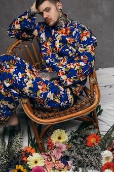 Una vista aérea del hombre joven relajado que se sienta en silla con las flores coloridas