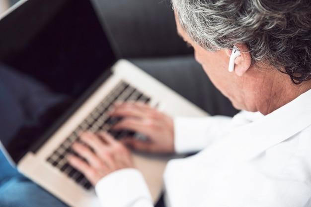 Una vista aérea del hombre mayor que lleva el auricular del bluetooth que usa el ordenador portátil