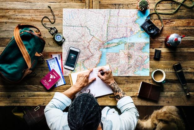 Vista aérea del hombre planeando el viaje escribiendo en un cuaderno