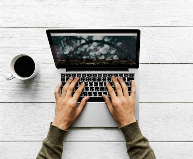 Vista aérea del hombre que usa una computadora portátil en el concepto de espacio de trabajo de mesa de madera
