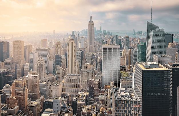 Vista aérea icónica de la ciudad de nueva york en un día soleado. rayos de sol entre los rascacielos y fondo nublado. concepto de viaje. nueva york, estados unidos.