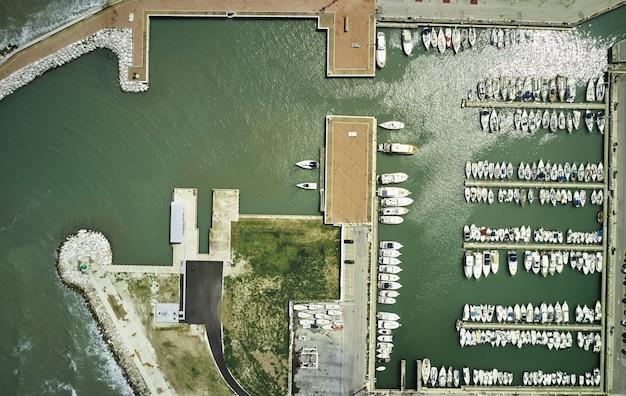 Vista aérea de increíbles barcos al atardecer en marina bay. vista superior desde drone del puerto con yate, lancha y velero. hermoso puerto