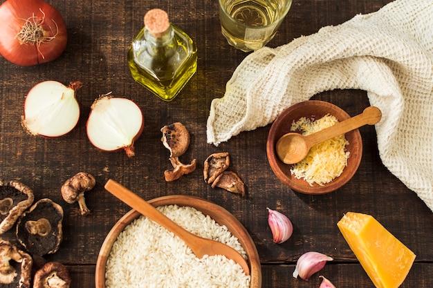 Una vista aérea de los ingredientes tradicionales del risotto italiano en la mesa de madera