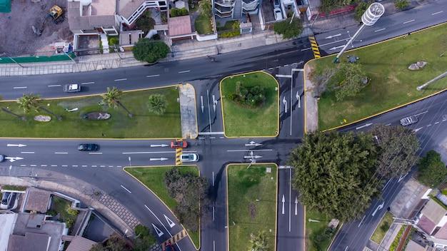 Vista aérea de una intersección con vehículos y líneas de cebra.