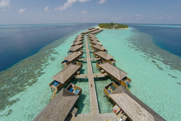 Vista aérea de una isla tropical en agua turquesa. luxurious over-water villas en la isla tropical de resort maldivas para el concepto de fondo de vacaciones de vacaciones -boost up procesamiento de color.