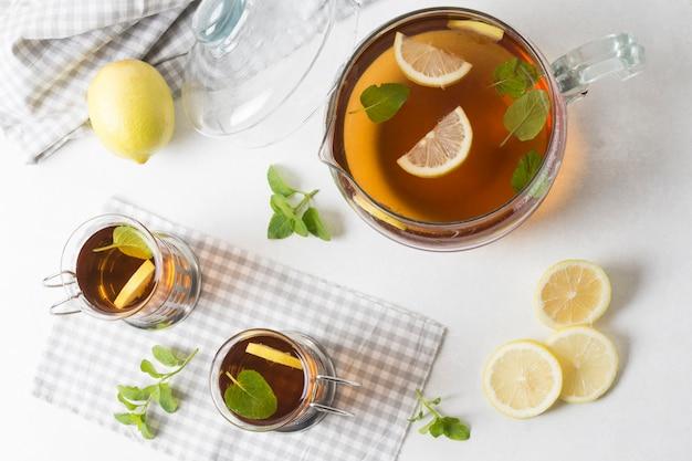 Una vista aérea de la jarra y vasos de té de hierbas con rodajas de limón y hojas de menta sobre fondo blanco