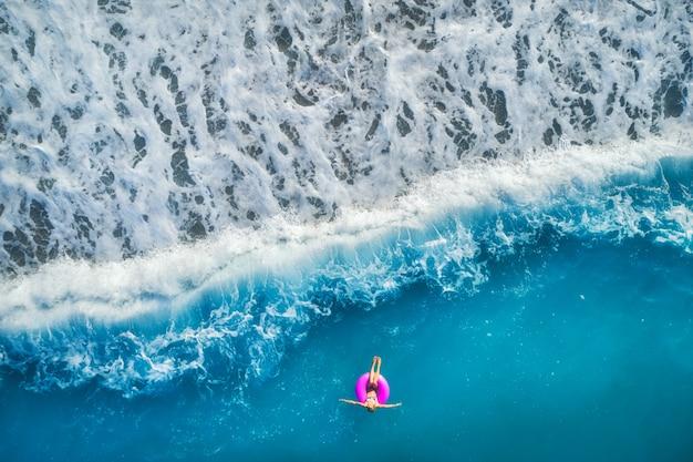 Vista aérea de la joven mujer nadando en el anillo de natación rosa