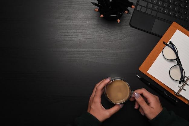 Vista aérea joven sosteniendo una taza de café en la mesa negra.