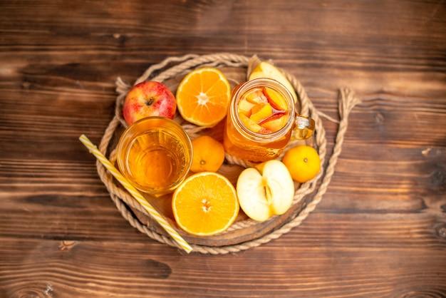 Vista aérea de jugo fresco orgánico en una botella y vaso servido con tubo y frutas sobre una tabla para cortar y sobre una mesa de madera marrón