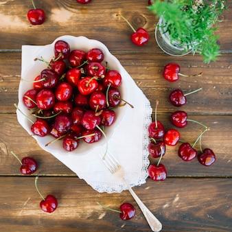 Vista aérea de jugosas cerezas rojas en un tazón sobre fondo de madera