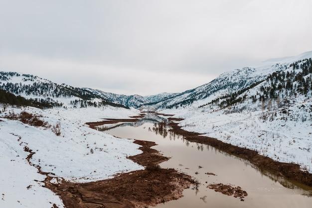 Vista aérea del lago de invierno en montañas nevadas