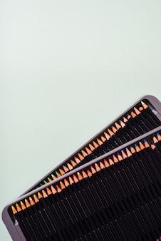 Una vista aérea de lápices de colores en una caja de metal abierta sobre fondo gris