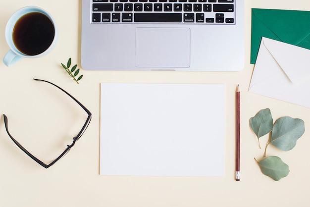 Vista aérea de una laptop con papelería y taza de té sobre fondo coloreado