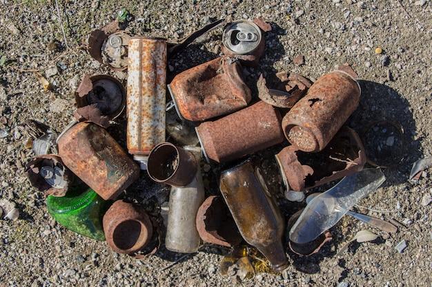 Vista aérea de latas oxidadas y botellas de vidrio, latas y botellas abandonadas, basura