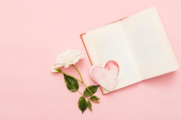 Vista aérea de libro con tarjeta en forma de corazón