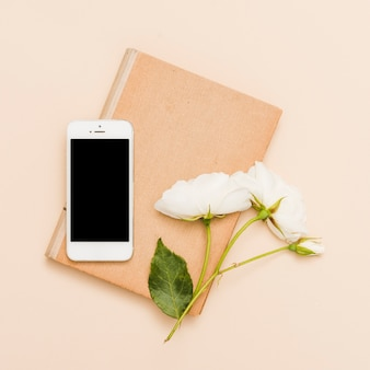 Vista aérea de libro, teléfono móvil y flores
