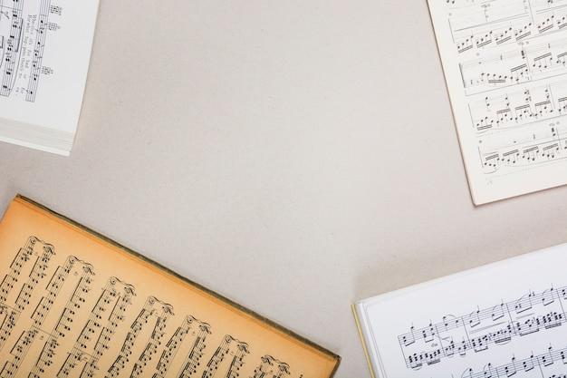 Una vista aérea de libros de notas musicales sobre fondo blanco con espacio para texto