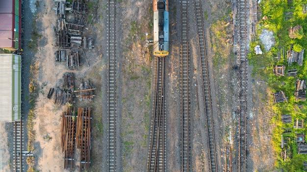 Vista aérea de la locomotora diesel tren y vías férreas - vista superior pov de escena conceptual industrial con trenes