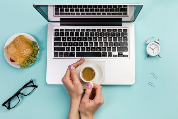 Una vista aérea de la mano de una empresaria sosteniendo una taza de café sobre la computadora portátil contra el fondo azul