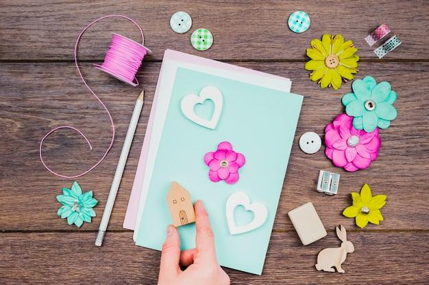 Una vista aérea de la mano humana que hace la tarjeta de felicitación con las flores y el bloque de madera de la casa en el escritorio