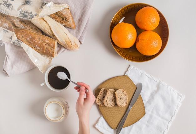 Vista aérea de la mano de una mujer que agrega leche en polvo a la taza de té con pan y naranjas sobre fondo blanco