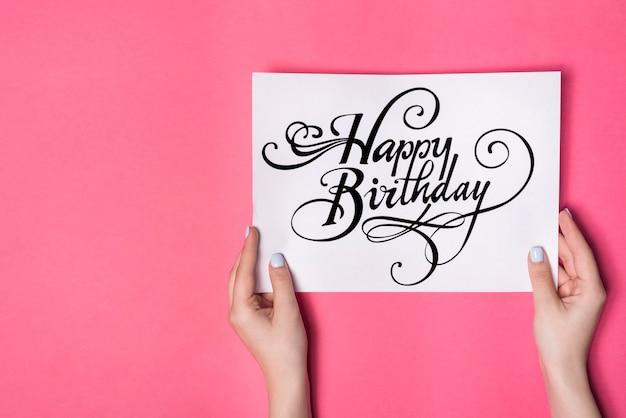Vista aérea de la mano de la mujer que sostiene la tarjeta del feliz cumpleaños contra el fondo rosa