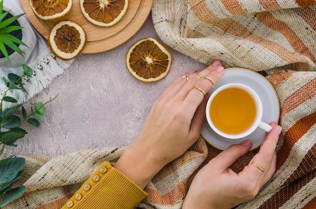 Una vista aérea de la mano de la mujer sosteniendo la taza de té de hierbas y el limón seco en el fondo texturizado