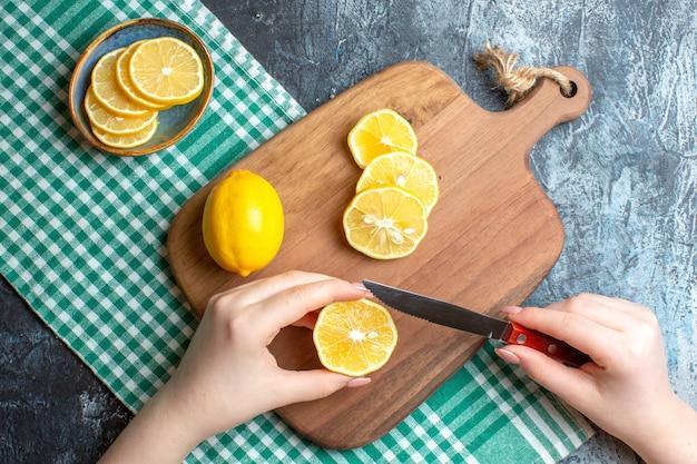 Vista aérea de una mano para picar limones frescos sobre una tabla de cortar de madera sobre fondo oscuro
